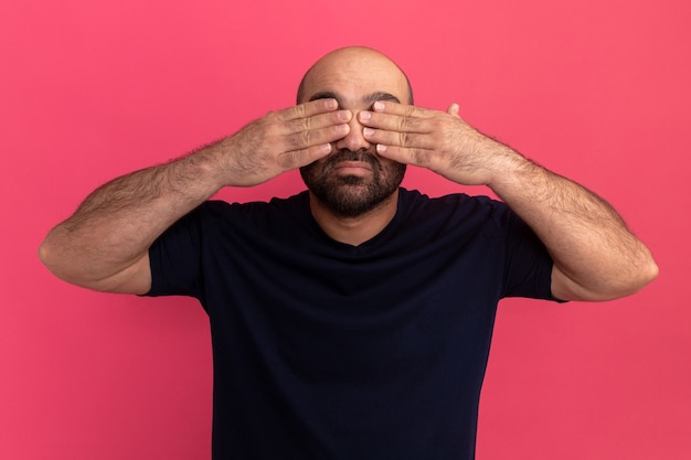 분홍색 벽 위에 서있는 손으로 눈을 덮고있는 해군 티셔츠에 수염 난 남자