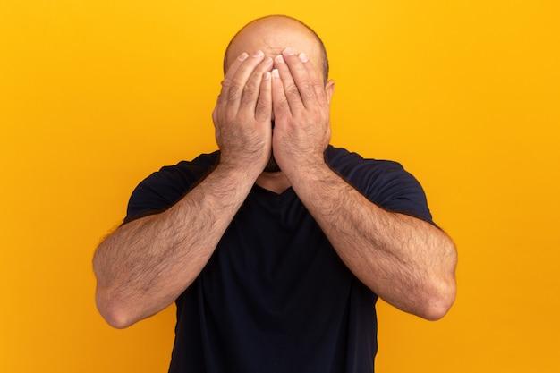 손으로 그의 얼굴을 덮고 해군 티셔츠에 수염 난 남자는 오렌지 벽 위에 서 우울