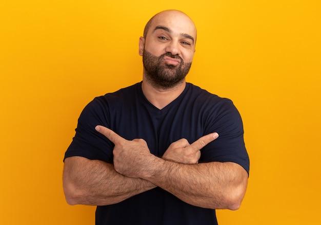 주황색 벽 위에 서있는 미소 측면을 검지 손가락으로 가리키는 해군 티셔츠 횡단 손에 수염 난된 남자