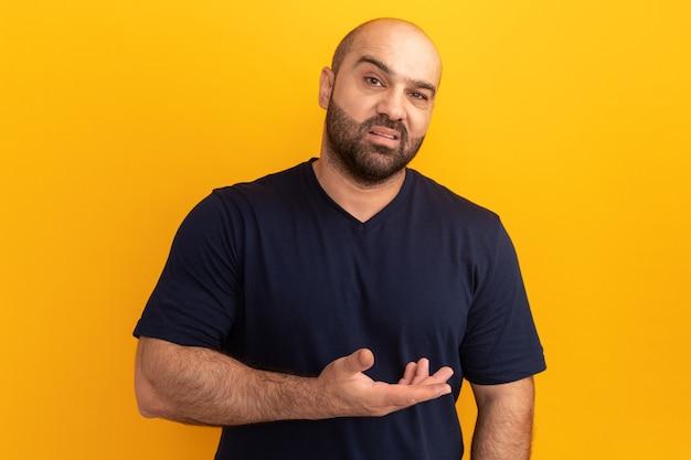 네이비 티셔츠를 입은 수염 난 남자는 불쾌하고 주황색 벽 위에 서서 분노한 팔로 혼란스러워합니다.