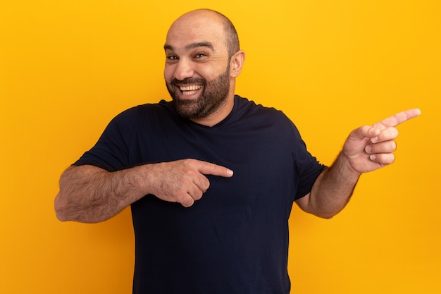 주황색 벽 위에 서있는 측면에 검지 손가락으로 가리키는 해군 티셔츠 행복하고 쾌활한 수염 난 남자
