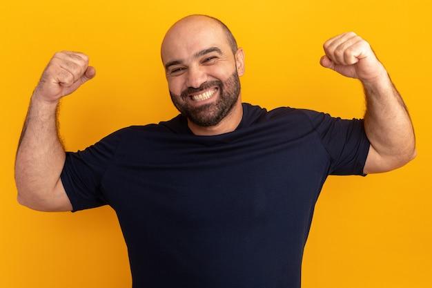 オレンジ色の壁の上に立っている勝者のように幸せで興奮したくいしばられた握りこぶしを上げる海軍のtシャツのひげを生やした男