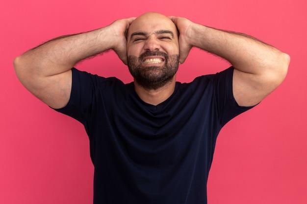 분홍색 벽 위에 서있는 그의 머리 뒤에 손으로 행복하고 흥분된 해군 티셔츠에 수염 난 남자