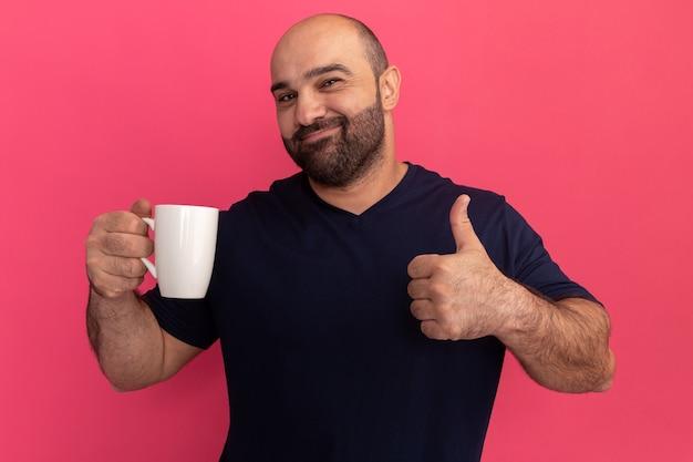 분홍색 벽 위에 서있는 컵 행복하고 긍정적 인 보여주는 엄지 손가락을 들고 해군 티셔츠에 수염 난 남자