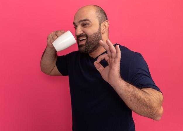 분홍색 벽 위에 서있는 확인 표시를 보여주는 행복하고 긍정적 인 마실 차 한 잔을 들고 해군 티셔츠에 수염 난 남자
