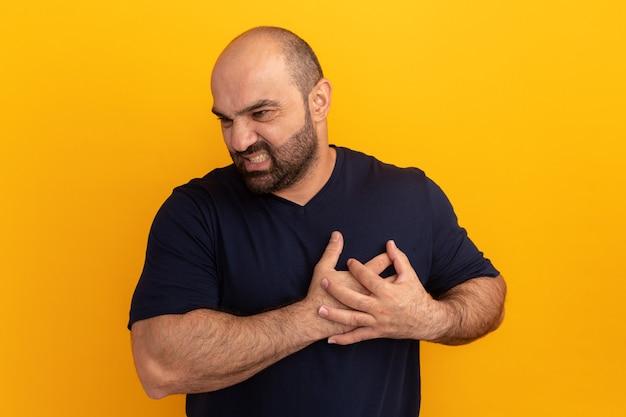 주황색 벽 위에 몸이 안 좋아 보이는 가슴에 손을 잡고 해군 티셔츠에 수염 난 남자