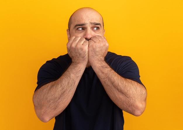 オレンジ色の壁の上に立っているストレスと神経質な噛む爪を脇に見ている海軍のtシャツのひげを生やした男