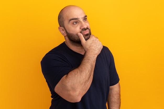 주황색 벽 위에 서있는 그의 턱에 손으로 잠겨있는 표정으로 옆으로 보이는 해군 티셔츠에 수염 난 남자