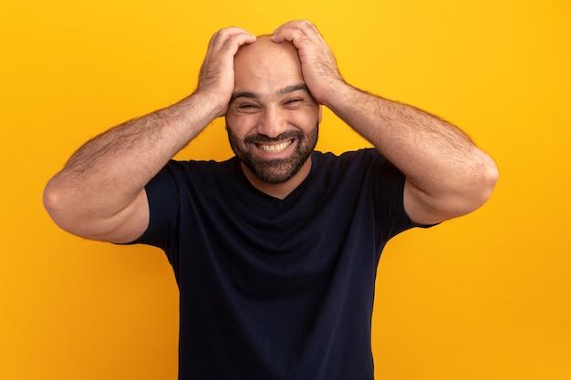 주황색 벽 위에 서있는 그의 머리에 손으로 혼란스럽고 좌절감을 느끼는 해군 티셔츠에 수염 난 남자