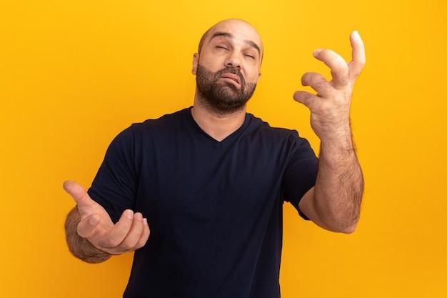 주황색 벽 위에 서있는 손으로 몸짓으로 혼란스러워하는 해군 티셔츠에 수염 난 남자