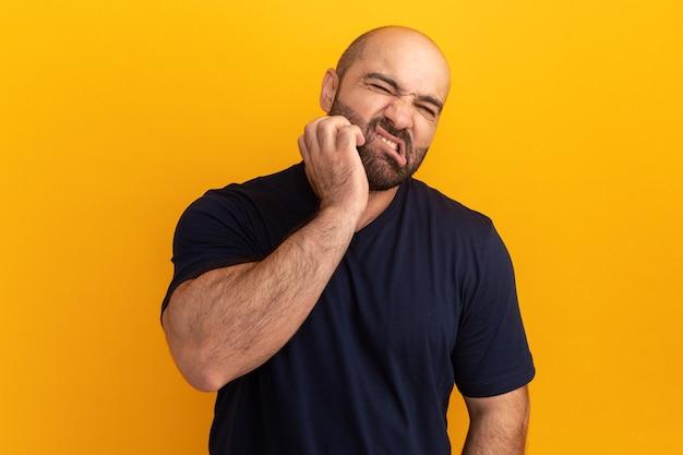 オレンジ色の壁の上に立っている彼の顔を引っかいて混乱しているように見える海軍のtシャツのひげを生やした男