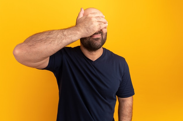 オレンジ色の壁の上に立っている手で疲れて退屈な目を覆っている海軍のtシャツのひげを生やした男