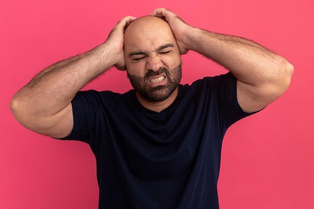 분홍색 벽 위에 서있는 두통으로 고통받는 그의 머리에 손이 불편 해 보이는 해군 티셔츠에 수염 난 남자