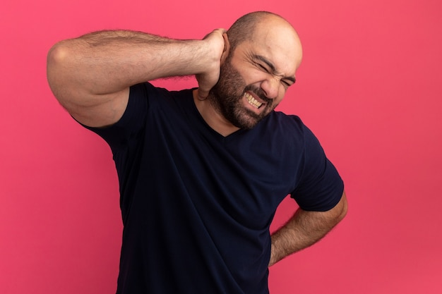 Бородатый мужчина в темно-синей футболке выглядит нездоровым, дотрагиваясь до шеи, чувствуя боль, стоя над розовой стеной