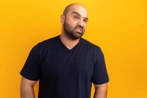 オレンジ色の壁の上に立っている失望した表情で苦い口を作る海軍のtシャツのひげを生やした男