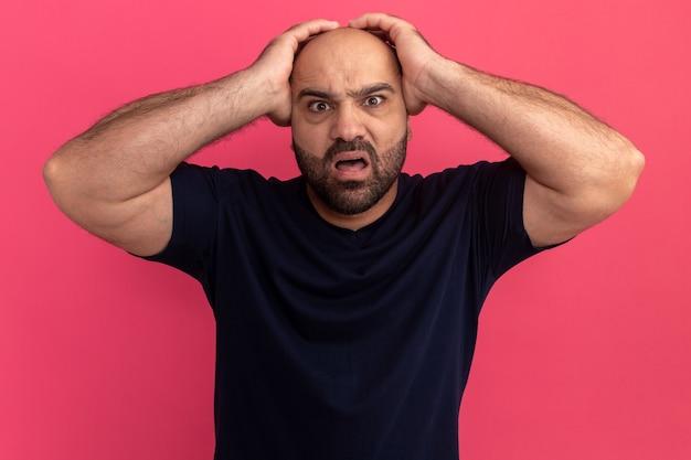 ネイビーのtシャツを着たひげを生やした男は、ピンクの壁の上に立って頭上に手を上げて驚いて心配