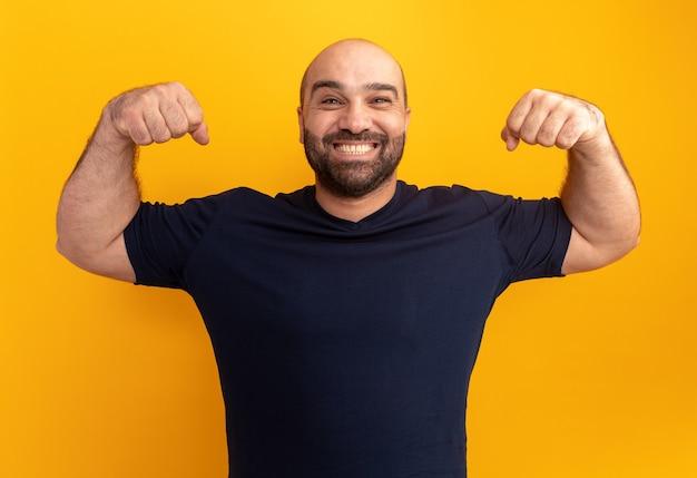우승자처럼 주먹을 올리는 해군 티셔츠에 수염 난 남자가 주황색 벽 위에 넓게 서서 행복하고 흥분된 미소
