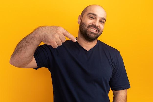 주황색 벽 위에 서있는 자신의 검지 손가락으로 자신감을 가리키는 해군 티셔츠에 수염 난 남자