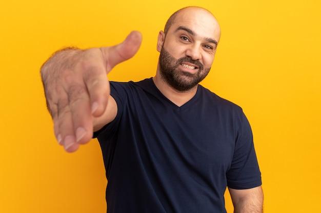 주황색 벽 위에 서있는 친절한 제안 손 인사 제스처 미소 해군 티셔츠에 수염 난된 남자