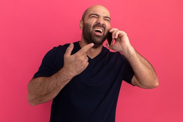 분홍색 벽 위에 서 좌절되는 외치는 휴대 전화에 말하는 해군 티셔츠에 수염 난된 남자