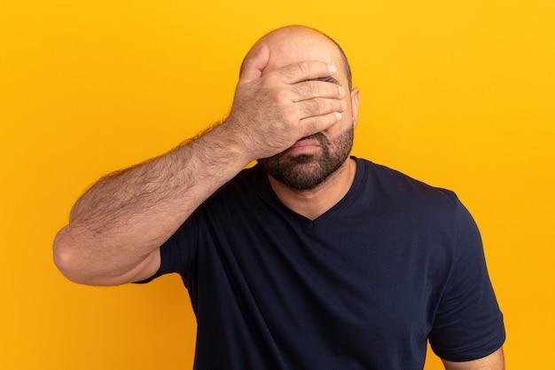 オレンジ色の壁の上に立っている手で疲れて失望した顔を覆っている海軍のtシャツのひげを生やした男