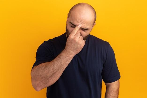 オレンジ色の壁の上に立っている頭痛で疲れて退屈している彼の額に触れている海軍のtシャツのひげを生やした男