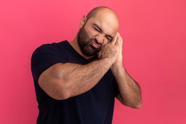 해군 티셔츠에 수염 난 남자는 분홍색 벽 위에 서있는 손바닥에 머리를 기대고 손바닥을 함께 들고 수면 제스처를 만들고 자고 싶어합니다.