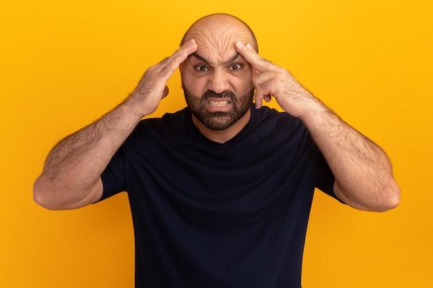 Бородатый мужчина в темно-синей футболке с сердитым лицом касается его головы, стоящего над оранжевой стеной