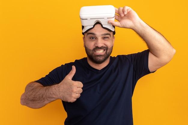 오렌지 벽 위에 서 엄지 손가락을 보여주는 가상 현실 행복하고 긍정적 인 미소의 안경 해군 티셔츠에 수염 난된 남자