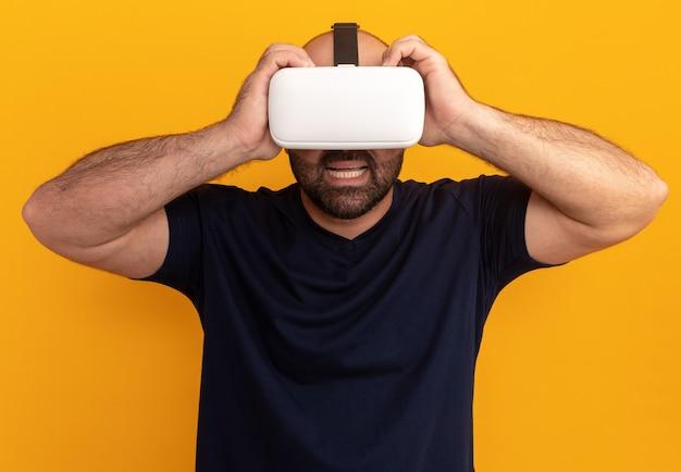 オレンジ色の壁の上に立って驚いて驚いたように見える仮想現実のメガネと海軍のtシャツのひげを生やした男