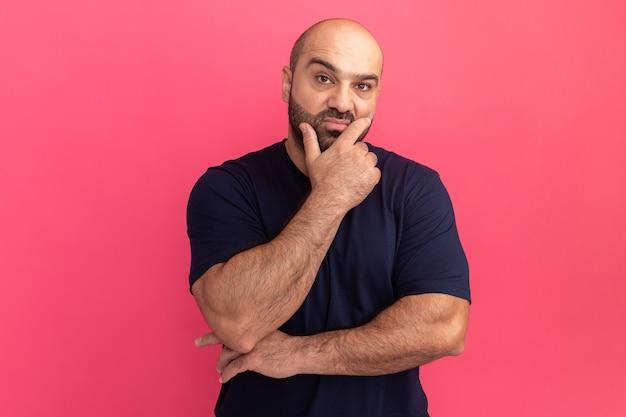 Бородатый мужчина в темно-синей футболке с рукой на подбородке думает, стоя над розовой стеной