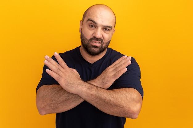 주황색 벽 위에 서있는 중지 제스처를 만드는 심각한 얼굴 횡단 손으로 해군 티셔츠에 수염 난 남자