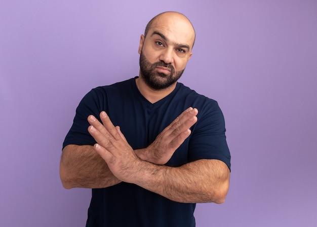 보라색 벽 위에 서있는 중지 제스처를 만드는 심각한 얼굴 교차 손으로 해군 티셔츠에 수염 난된 남자