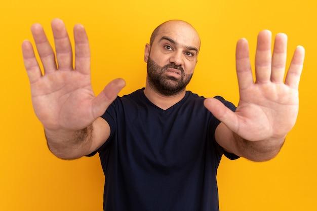 오렌지 벽 위에 서있는 손으로 심각한 얼굴 만들기 중지 제스처와 해군 티셔츠에 수염 난된 남자