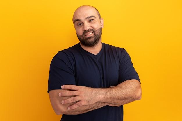 Бородатый мужчина в темно-синей футболке со скептической улыбкой на лице со скрещенными руками стоит над оранжевой стеной