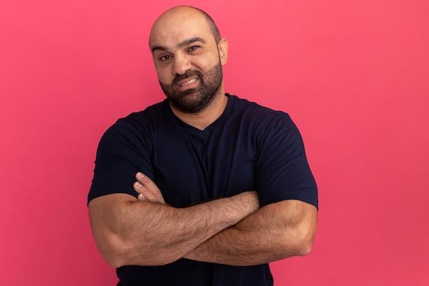 Бородатый мужчина в темно-синей футболке с улыбкой на лице со скрещенными руками стоит над розовой стеной