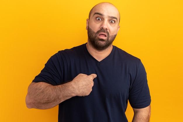 ネイビーのtシャツを着たひげを生やした男性は、オレンジ色の壁の上に立っている人差し指で指さして心配し、驚いた