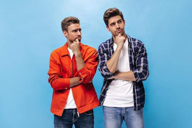 オレンジ色のジャケットを着たひげを生やした男性と市松模様のシャツを着た彼の友人は、思慮深く見え、孤立した青い壁にポーズをとっています。