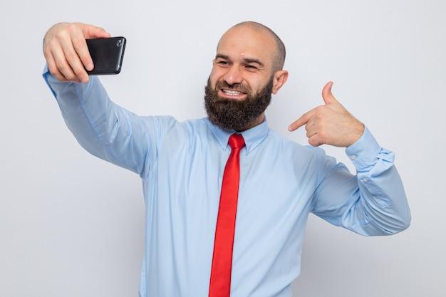 빨간 넥타이와 파란 셔츠를 입은 수염 난 남자는 스마트폰을 사용하여 셀카를 찍고 행복하고 흥분하여 자신을 가리키며 즐겁게 웃고 있습니다.