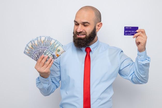 赤いネクタイと青いシャツを着たひげを生やした男は、白い背景の上に元気に立って幸せで幸せな笑顔でお金を見て現金とクレジットカードを保持しています。