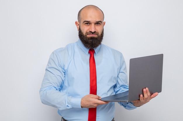 赤いネクタイと青いシャツのひげを生やした男は、白い背景の上に自信を持って幸せで前向きに立って笑顔のカメラを見てラップトップを保持しています。
