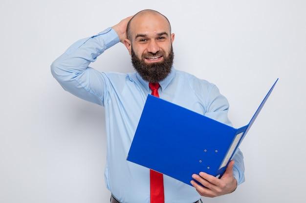 赤いネクタイと青いシャツを着たひげを生やした男は、白い背景の上に立っている彼の頭に手で元気に笑顔で幸せで興奮してカメラを見てオフィスフォルダーを保持しています