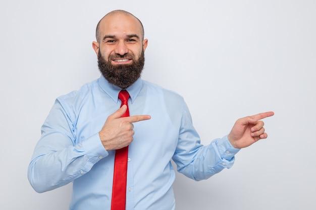 빨간 넥타이와 파란 셔츠를 입은 수염 난 남자가 카메라를 바라보며 행복하고 긍정적인 미소를 지으며 검지 손가락으로 흰색 배경 위에 서 있는 쪽을 즐겁게 가리키고 있습니다.