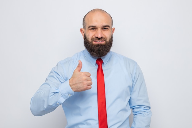 Бородатый мужчина в красном галстуке и синей рубашке выглядит уверенно улыбаясь, показывает палец вверх