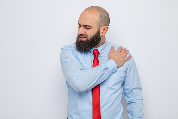 빨간 넥타이와 파란 셔츠를 입은 수염 난 남자는 흰색 배경 위에 서 있는 고통을 느끼고 어깨를 만지는 몸이 좋지 않은 것처럼 보입니다.