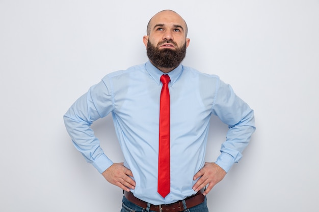 白い背景の上に立っている腰に手で困惑して見上げる赤いネクタイと青いシャツのひげを生やした男