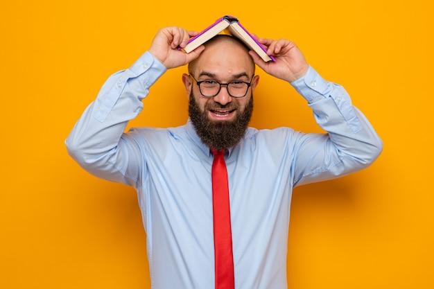 彼の頭の上に本を保持している眼鏡をかけている赤いネクタイと青いシャツのひげを生やした男はオレンジ色の背景の上に元気に立って幸せで面白い笑顔