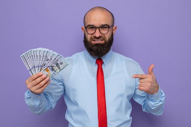 赤いネクタイと青いシャツを着たひげを生やした男は、紫色の背景の上に元気に立って笑顔のカメラを見て人差し指でお金を指して現金を保持している眼鏡をかけています