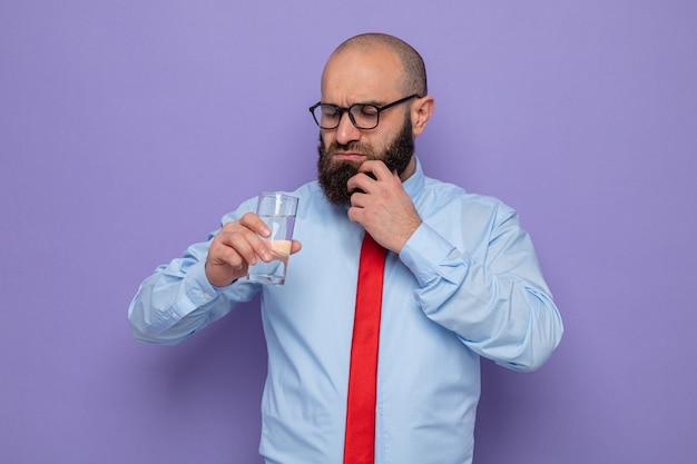 赤いネクタイと青いシャツのひげを生やした男は、紫色の背景の上に立って困惑した深刻な顔でそれを見て水のガラスを保持している眼鏡をかけています