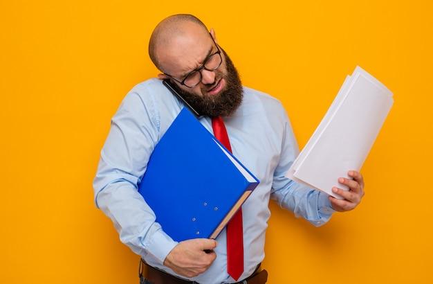 사무실 폴더와 문서를 들고 있는 안경을 쓰고 빨간 넥타이와 파란색 셔츠를 입은 수염 난 남자는 바쁘고 휴대 전화로 이야기하는 데 스트레스를 받습니다.